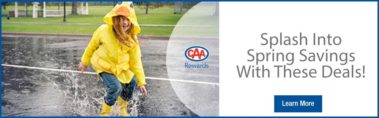 girl splashing in a puddle with yellow rain coat and yellow boots